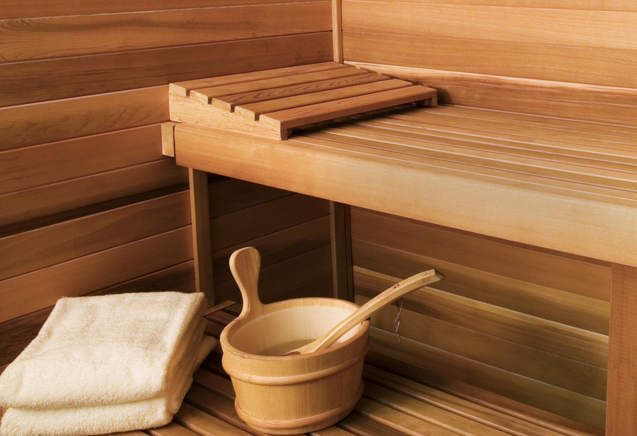Close-up shot of inside of sauna showing bench, towels and pail.